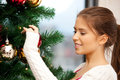 Woman decorating christmas tree bright picture of Stock Photos