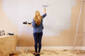 Woman Decorating Room Using Paint Roller On Wall Royalty Free Stock Photo