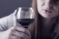 Woman in depression young beautiful drinking alcohol on dark background Royalty Free Stock Photo