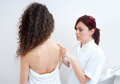 Woman at dermatology examination dermatologist doctor inspecting women skin for moles and melanoma Royalty Free Stock Photo