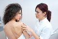 Woman at dermatology examination dermatologist doctor inspecting women skin for moles and melanoma Stock Photo