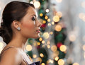 Woman with diamond earring over christmas lights Royalty Free Stock Photo