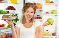 Woman on diet to choose between healthy and unhealthy food near a refrigerator Stock Images