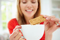Woman dipping biscuit into hot drink at home whilst sitting down Stock Photo