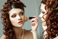 Woman directs a make up the young in the morning before wedding Stock Photos