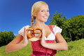 Woman in dirndl in bavarian smiling happy holding a pretzel a landscape Royalty Free Stock Photography