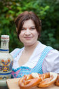 Woman in dirndl dress holding beer and pretzel Royalty Free Stock Images