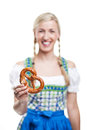 Woman in a dirndl holding a pretzel beautiful smiling young blond or salted glazed brittle german biscuit the shape of knot Royalty Free Stock Photo