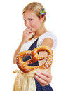 Woman in dirndl offering pretzel shy bavarian a a fresh Stock Photo