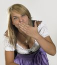 Woman in a dirndl smiling blond wearing traditional dress named and blowing kiss Royalty Free Stock Photography