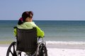 Woman disability beach handicapped sits disabled in her wheelchair at the Royalty Free Stock Photography