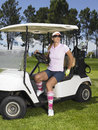 Woman disembarking from golf cart beautiful female golfer wearing sunglasses Stock Image