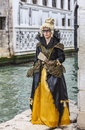 Woman disguised venice italy march a in a beautiful costume with a colmbina mask pose on the edge of a water canal in venice Royalty Free Stock Images