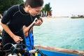 Woman diver testing regulator before scuba diving Royalty Free Stock Photo