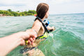 Woman with diving googles dragging partner to the sea Royalty Free Stock Photo