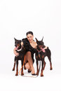 Woman with doberman young in elegant dress two female studio shot full body shot Stock Photography