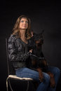 Woman with dobermann dog on black background Stock Photos
