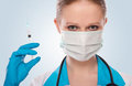 Woman doctor in a mask with a syringe Stock Images