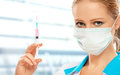 Woman doctor in a mask with a syringe with a vaccine close up Royalty Free Stock Images