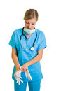 Woman in doctor uniform wearing latex gloves Stock Photo