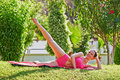 Woman does leg swing lying on matting young in morning garden Royalty Free Stock Photos