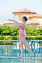 Woman does morning exercises on poolside young Stock Photo
