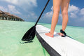 Woman does stand up paddle boarding on the ocean in Maldives Royalty Free Stock Photo