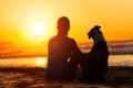 Woman and dog looking summer sun relaxed enjoying sunset or sunrise over the sea sitting on the sand at the beach Stock Image