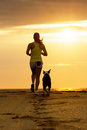 Woman and dog running on sunset toward the sun summer beach in a beautiful golden sport girl her pet training together Royalty Free Stock Photo