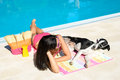 Woman and dog at swimming pool sunbathing together on funny summer like if they were talking to each other beautiful girl her Stock Photos
