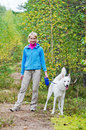 Woman with a dog walk in an autumn wood Stock Images