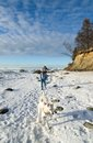 Woman with a dog walk on a sunny winter day the coast of the sea Royalty Free Stock Photos