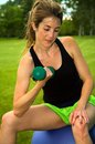 Woman doing bicep curls young on an exercise ball in a park Royalty Free Stock Photography