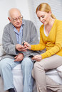 Woman doing blood glucose monitoring for senior men at home Stock Photography