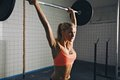 Woman doing crossfit barbell lifting strong as a part of exercise routine fit young heavy weights at gym Stock Photo
