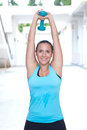 Woman doing double extension with a dumbbel raised above her head sporty Stock Photography