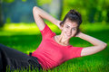 Woman doing exercises for abdominal muscles strength at outdoor sport exercise smiling happy yoga stretches after running Royalty Free Stock Photography