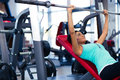 Woman doing exercises with barbell on the bench Royalty Free Stock Photo