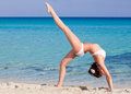 Woman is doing flexibility exercise on the beach Stock Photo