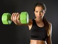 Woman doing front shoulder fly photo of a beautiful female a with a dumbbell over a dark background Stock Photo
