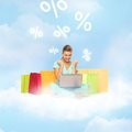 Woman doing internet shopping and future technology concept with laptop bags and credit card on the cloud Royalty Free Stock Images