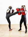 Woman doing kick boxing young women learning self defense martial arts Stock Photos