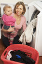 Woman Doing Laundry And Holding Daughter Royalty Free Stock Photos