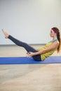Woman doing navasana yoga pose on exercise mat Royalty Free Stock Photo