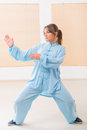 Woman doing qi gong tai chi exercise beautiful wearing professinal oryginal chinese clothes at gym Royalty Free Stock Photos