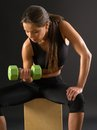 Woman doing seated dumbbell curl photo of an attractive female a while sitting Stock Images
