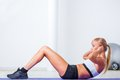 Woman doing sit ups on the floor blonde Royalty Free Stock Photo