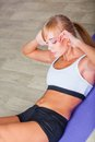 Woman doing sit ups on the floor blonde Stock Images