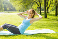Woman doing situps in park female fitness instructor exercising sit ups on yoga mat outside green summer Royalty Free Stock Photos