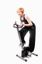 Woman doing sports on exercise bike Stock Images